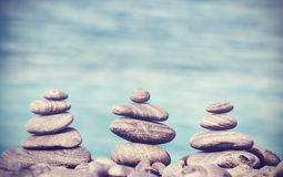 Vintage retro hipster style image of stones on beach. Stock Photos