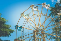 Close up part of colorful ferris wheel with green tree and blue sky background. Royalty Free Stock Images