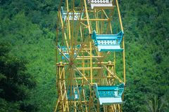Close up part of colorful ferris wheel with green trees background at green park. Royalty Free Stock Photos