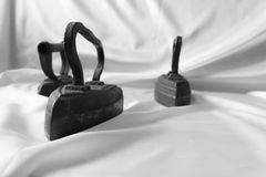 Vintage retro iron. Three ancient iron on the white cloth. Iron caressing the white fabric. Beautiful irons from the past stock photos