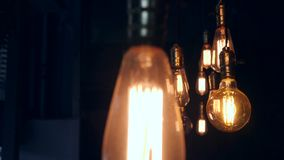 Vintage Retro Lamp Bulbs Lighting Decoration in Loft Style. Old School Lights Hanging on Ceiling in Cafe. Light in the. Dark. 4K stock footage