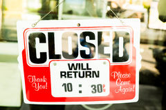 Vintage retro looking Closed sign in a shop showroom. With reflections Stock Photo