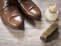 Vintage retro a pair of men brown leather shoes on a wooden flo. Vintage retro a pair of men brown leather shoes and shoe polish, brushes on a wooden floor ( Royalty Free Stock Image