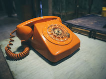 Vintage Retro phone orange color on table Royalty Free Stock Image