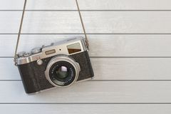Vintage retro photo camera hanging on the white wooden wall. Stock Images
