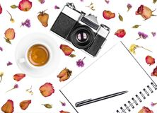 Vintage retro photo camera, notepad, pen, coffee cup and dried flowers isolated on white background. Flat lay, top view Royalty Free Stock Photography