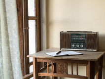 Vintage retro radio, notebook and pen on wooden table Royalty Free Stock Image
