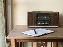 Vintage retro radio, notebook and pen on wooden table Royalty Free Stock Photos