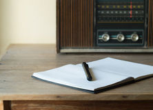 Vintage retro radio, notebook and pen on wooden table Royalty Free Stock Images