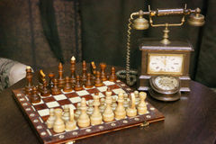 Vintage retro still life with dial phone and chess Stock Photo