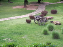 Vintage retro style used wood metal cart standing on green grass garden Royalty Free Stock Photo