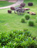 Vintage retro style used wood metal cart standing on green grass garden Stock Image