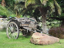 Vintage retro style used wood metal cart standing on green grass garden Royalty Free Stock Image