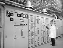 Vintage Retro Technology, Engineer, Scientist. Vintage retro scene of an engineer or scientist working with old technology. The smart man is looking at power stock image