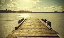 Vintage retro toned image of a pier on frozen lake. Stock Images