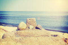 Vintage retro toned simple sandcastle on a beach, summer holiday Stock Photos