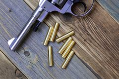 Vintage revolver Nagant with a rotating drum and the seven golden cartridges. On textured old boards royalty free stock image