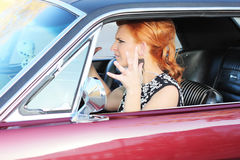Vintage Road Rage. Angry red head woman with sixties makeup and wardrobe driving in retro muscle car waving hands in frustration Stock Photos