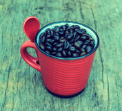 Vintage  roasted  coffee  beans in red cup on the old background Royalty Free Stock Photo