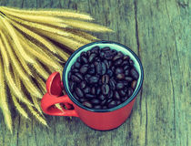 Vintage  roasted  coffee  beans in red cup on the old background Royalty Free Stock Image