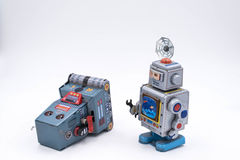 Vintage Robot Toy Repairing Another on a White Background.  Stock Images