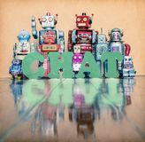 Chat robots. Vintage robot toys with the word CHAT on an old fooden floor Royalty Free Stock Image