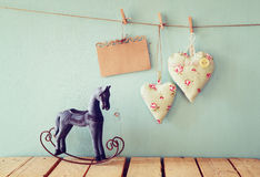 Vintage rocking horse next to fabric hearts and empty card for adding text hanging on the rope on wooden floor Stock Images