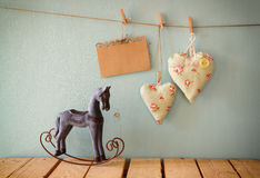 Vintage rocking horse next to fabric hearts and empty card for adding text hanging on the rope on wooden floor Royalty Free Stock Photography