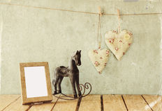vintage rocking horse next to fabric hearts hanging on the rope Stock Images