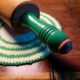 Vintage rolling pin with green handle on vintage crocheted potholder. Royalty Free Stock Photography