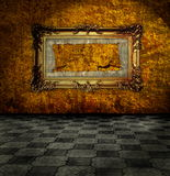 Vintage room. Carved gilded frame on gold wall Stock Photography