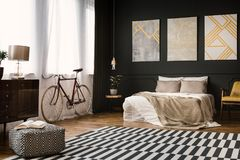 Vintage room with bed. Vintage room interior with bed, bike, carpet on the floor and pouf Royalty Free Stock Photo