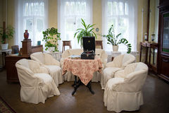 Vintage room with phonograph. Chairs in white covers, sofa, round table, window, vinyl records Stock Images