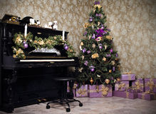 Vintage room with a piano, Christmas tree, candles, gifts  or pr Royalty Free Stock Image