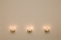 Vintage room with three antique wall lamps. Stock Photo