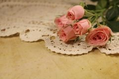 Vintage roses on a lace napkin and old paper Royalty Free Stock Photo