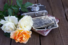 Vintage roses, old photos and camera on a wooden background Royalty Free Stock Photos