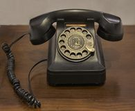 A vintage rotary dial telephone on an old wooden table royalty free stock image