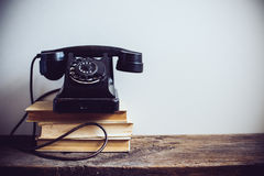 Vintage rotary phone. Black vintage rotary phone and books on rustic wooden table, on a white wall background stock images