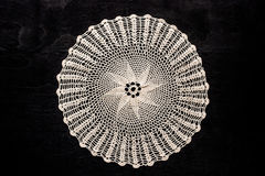 Vintage round lace napkin on the black wooden table Stock Image