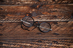 Vintage round reading glasses. On a wooden background Royalty Free Stock Photo