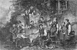 Tinker workshop on the street, vintage engraving. Vintage rural lifestyle; the tinkerer working in a yard surrounded by curious people Royalty Free Stock Photo