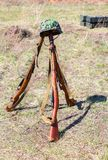 Vintage Russian military rifles Mosin system, model of 1938 an. D German helmet at the battle field Royalty Free Stock Photography