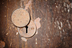 Vintage rust metal keyhole decorative element on weathered woode. N surface for background Stock Photos