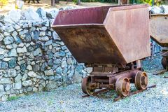 Vintage Rusted Mining Ore Cart. Vintage Rusted Ore Cart In Mining Operations Yard Next To Rock Wall stock photography
