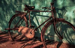 Vintage rustic metallic bicycle with blue wall as a background with light and shadow can be used as a advertising royalty free stock photos
