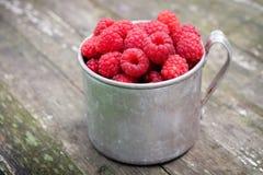 Vintage rustic mug full of raspberry berries. royalty free stock image