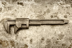 Vintage rusty adjustable spanner on an old iron background Stock Photography