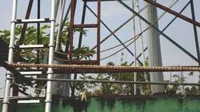 Vintage Rusty Clothes Rack com as escadas velhas do metal sobre a parede verde suja Fotografia de Stock Royalty Free