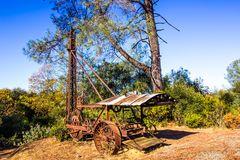 Vintage Rusty Drilling Equipment On Hill. Vintage Rusty Drilling Equipment With Large Iron Wheels Abandoned On Side Of Hill stock image